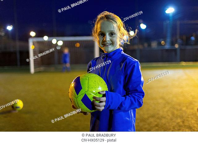 Portrait confident girl soccer player on field at night