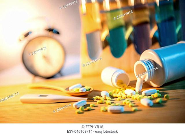 Pills spilling out of pill bottles with digital thermometer and pharmaceutical spoon on wooden board. Table clock and test tube in the background