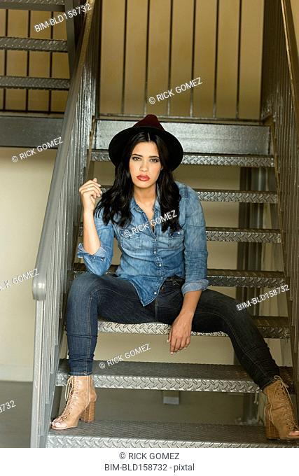 Glamorous Hispanic woman sitting on staircase