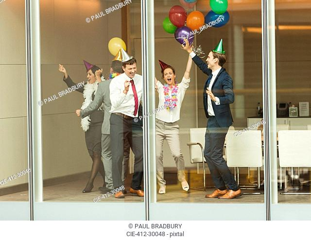 Business people wearing party hats and dancing with balloons at conference room window