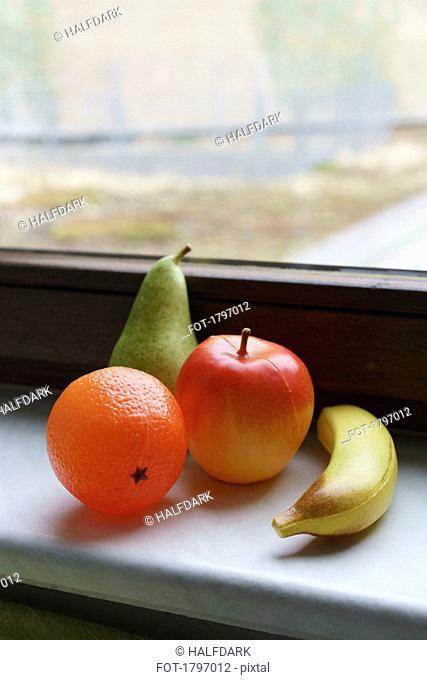 Plastic fruits on windowsill