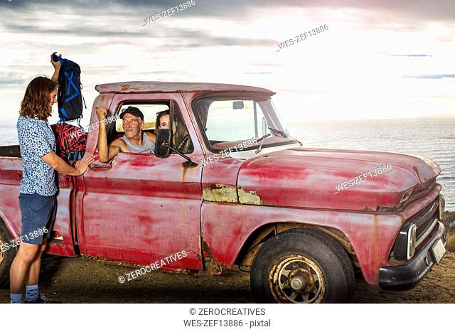 Young man taking his belongings from an old pick up at the coast