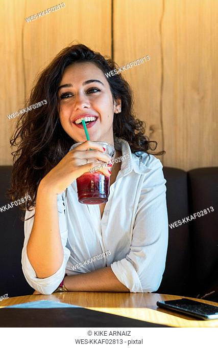 Portrait of happy young woman drinking smoothie