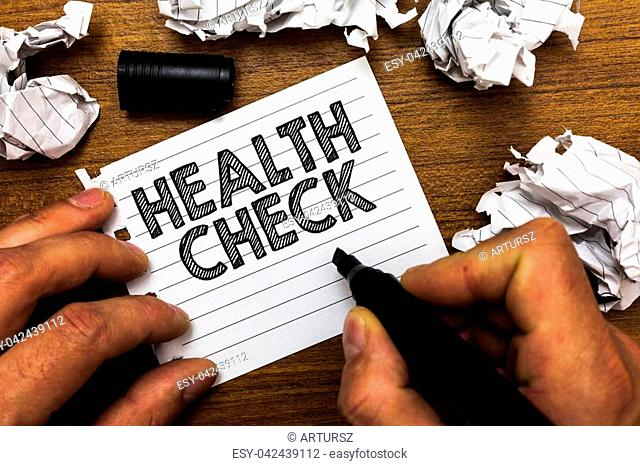 Text sign showing Health Check. Conceptual photo Medical Examination Wellness and general state Inspection Man holding marker notebook page crumpled papers...