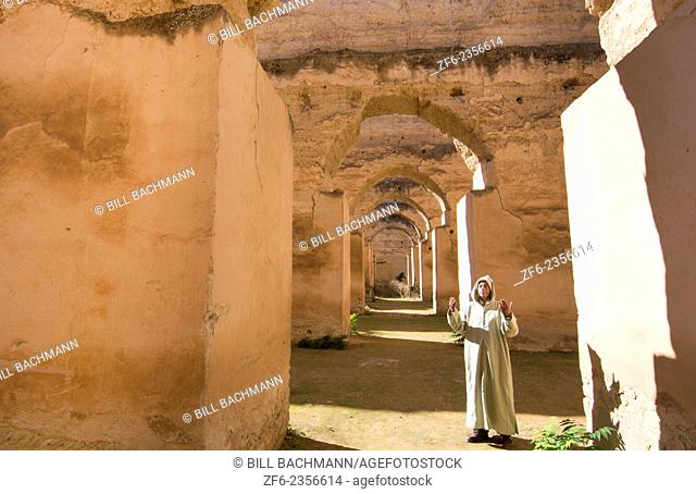 Meknes Morocco columns of Hri Souani former horse stalls in 17th century with arab man in robe in downtown with sunlight