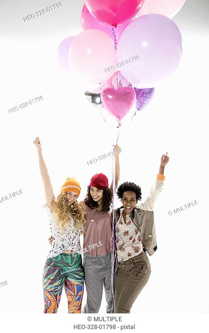 Portrait enthusiastic women friends cheering and holing multicolor balloons against white background