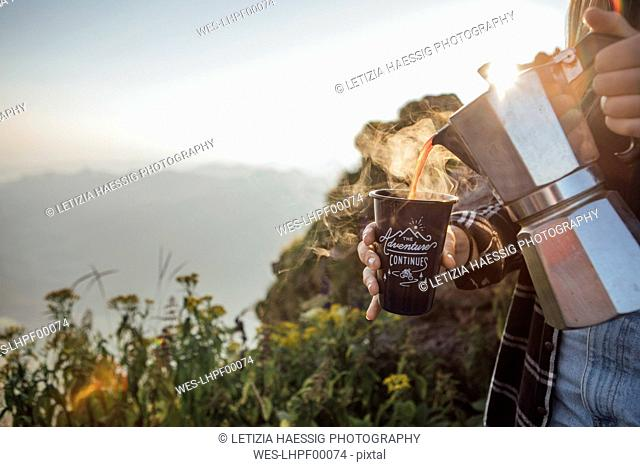 Close-up of woman on a hiking trip at sunrise pouring coffee into a cup