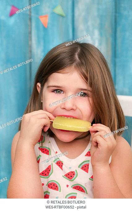 Portrait of little girl eating lemon ice lolly