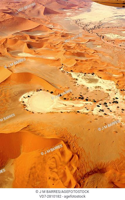 Aerial photography of Namib desert dunes with pans (endorheic drainage basins) produced by ephemeral Tsauchab River. Dune is a hill of loose sand carried for...