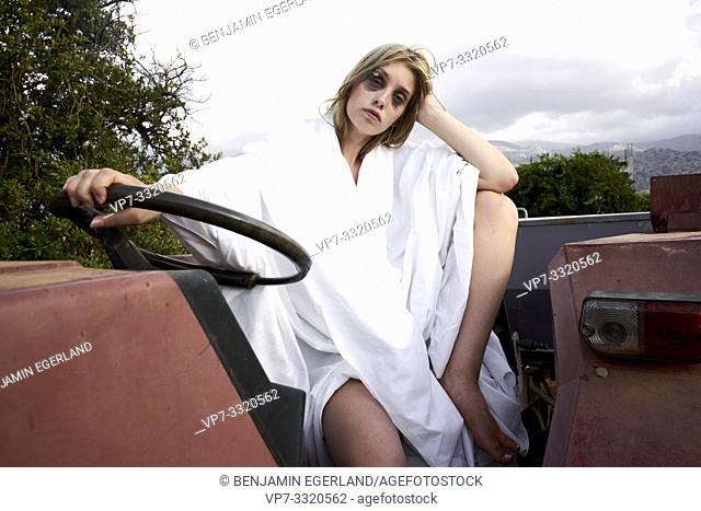 young defaced teenage woman with black eye sitting on tractor at farm, scars