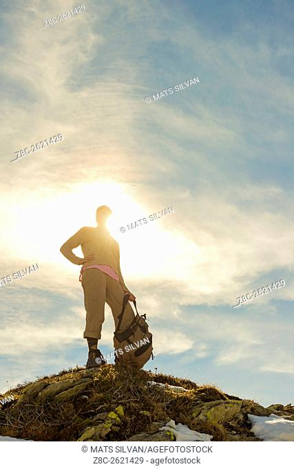 Woman with her backpack standing on a mountain top and sunshine in Grisons, Switzerland