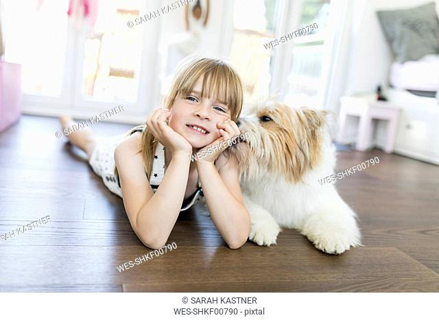 Girl with dog lying on the floor at home