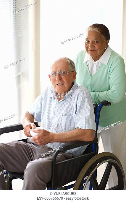 Portrait of a senior citizen couple at a hospital , man on the wheelchair