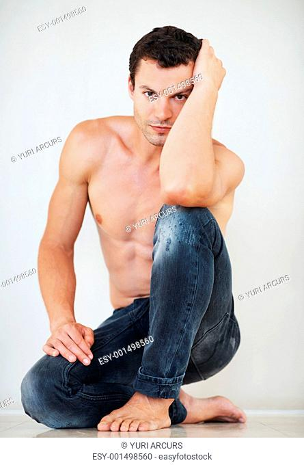 Portrait of sexy shirtless man sitting down on floor
