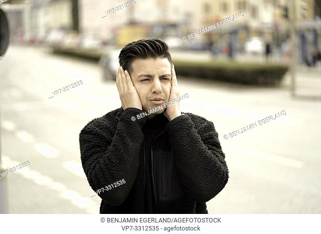 young man, hands covering ears, in Munich, Germany