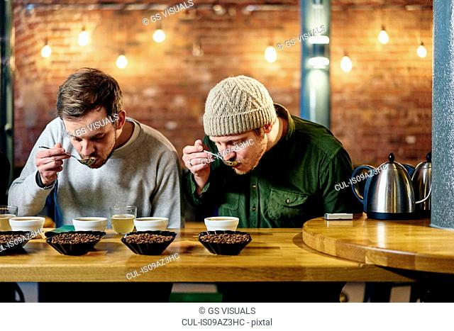 Coffee shop team slurping bowls of coffee and coffee beans at tasting
