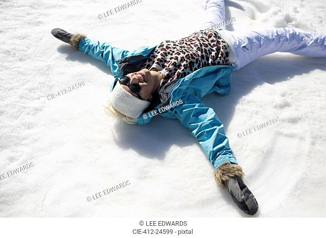 Happy woman making snow angels