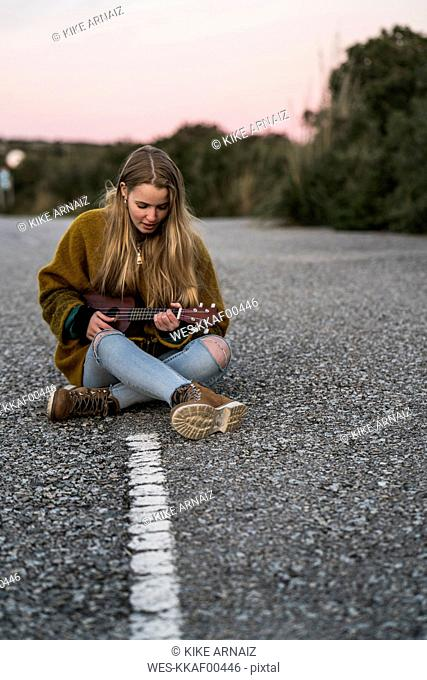 Young woman playing ukulele on a road