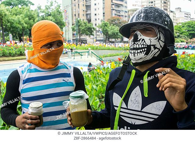 """Two young man shows a jar containing feces, also called """"""""Puputov"""""""" to throw against the police or national guard. Under the motto """"""""Our Shield is the..."""