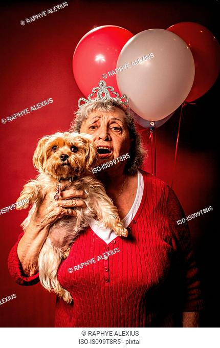 Senior woman holding dog and wearing a tiara