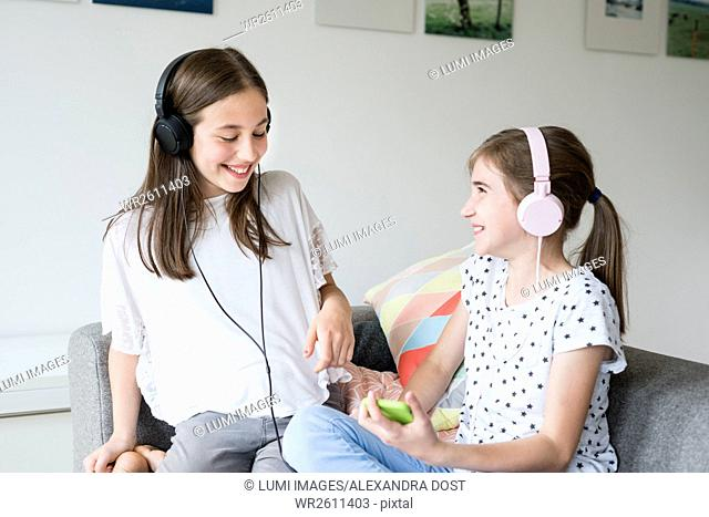 Two teenage girls with headphones listening to music