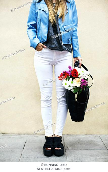 Young woman standing with bunch of flowers in her bag