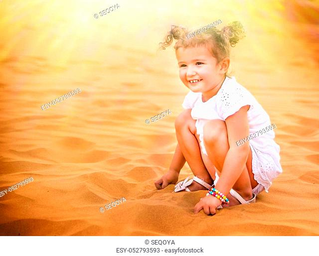 Little girl smiles and plays sand in the desert