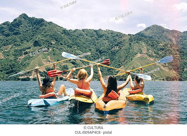 Rear view of four female friends celebrating in kayaks on Lake Atitlan, Guatemala