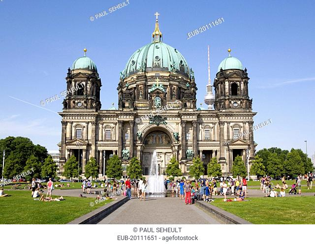 Mitte Museum Island. Berliner Dom Berlin Cathedral. people cooling down in a fountain in Lustgarten in front of the church with copper green domes and the...