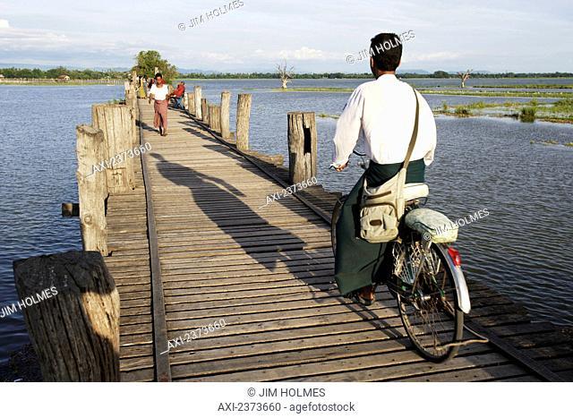 Cyclist goes across U Bein Bridge, made of Teak wood; Mandaly, Burma