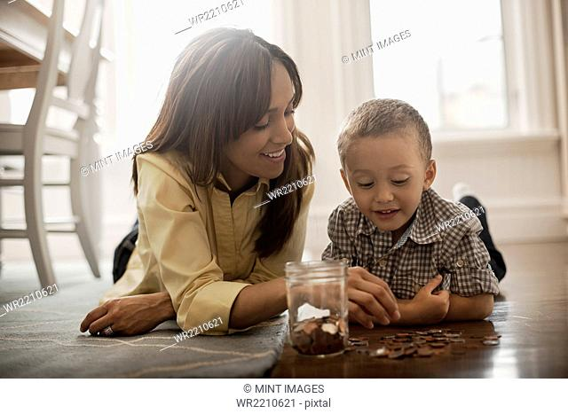 A woman and a child lying on the floor, playing with brass and silver coins, putting them into a glass jar