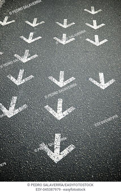 Directional arrows painted on a cement floor