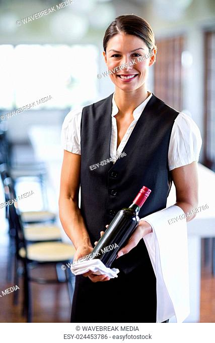 Waitress holding a bottle of red wine and a towel