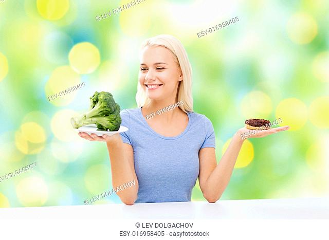 healthy eating, junk food, diet and choice people concept - smiling woman choosing between broccoli and donut over summer green holidays lights background
