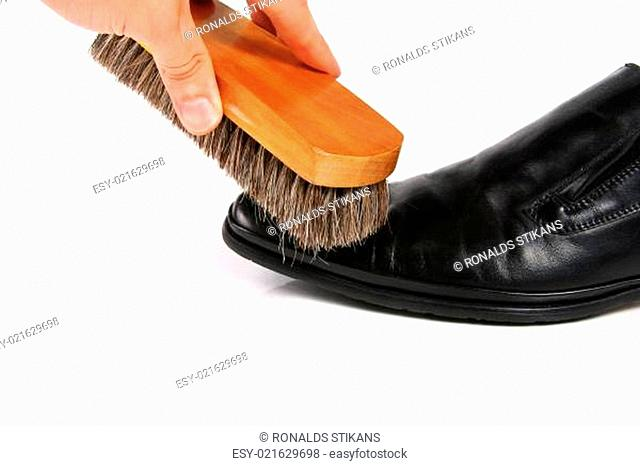 hand with brush cleaning shoe