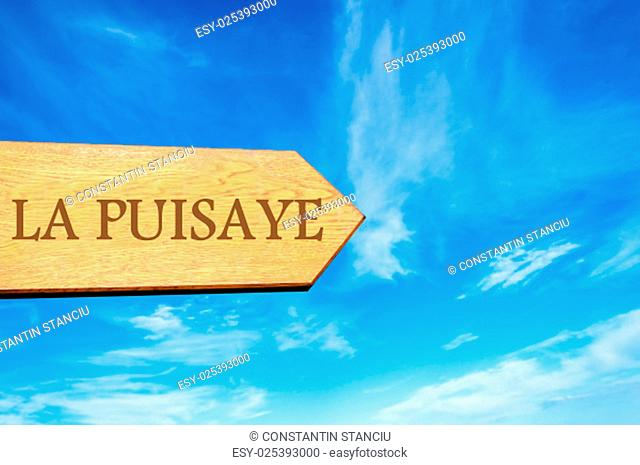 Wooden arrow sign pointing destination LA PUISAYE, FRANCE against clear blue sky with copy space available. Travel destination conceptual image