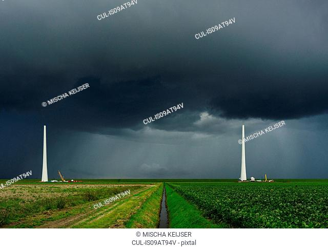 Thunderstorm approaching wind turbines under construction, Netherlands