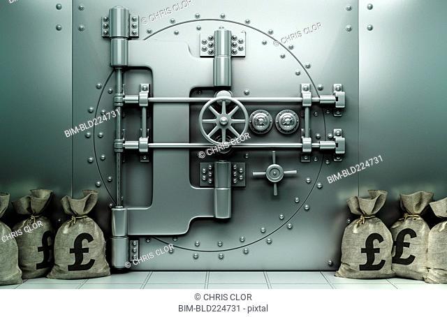Money bags with British pound symbol on floor near vault