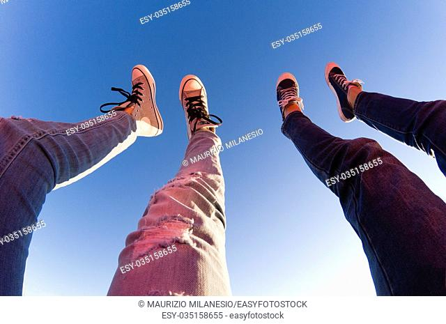 Young couple lifts their legs towards clear blue sky
