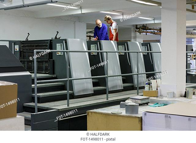 Mature worker talking with colleague at equipment in printing press