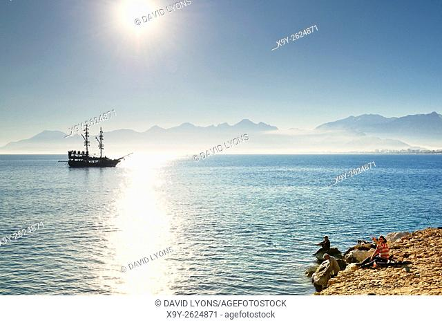 Antalya, Turkey. Looking west from entrance of Kaleici harbour. Fishermen and tourist sightseeing boat