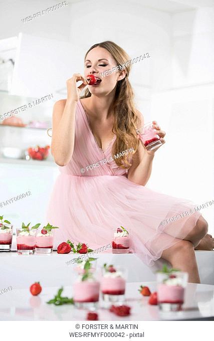 Germany, Young woman biting strawberry, glasses with strawberry yogurt