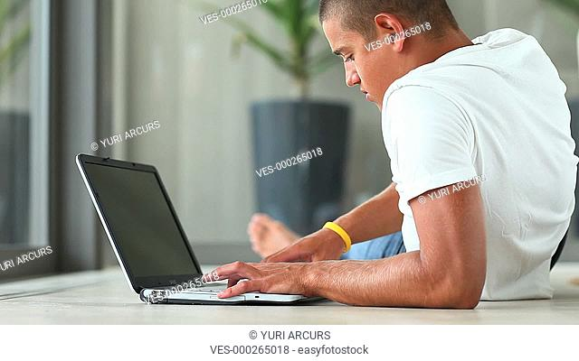 A relaxed young man lying in his lounge while typing on his laptop
