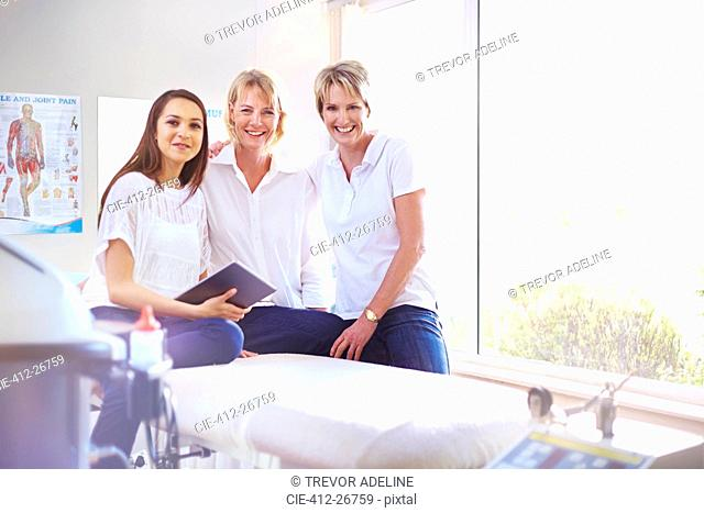 Portrait smiling physical therapists in examination room