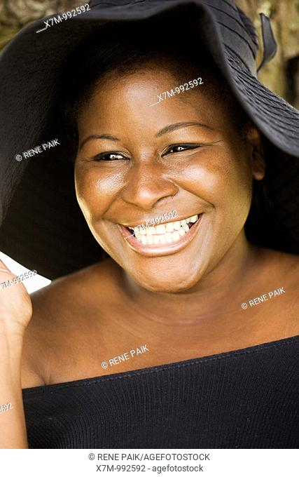 A happy black woman wears a hat for sun protection