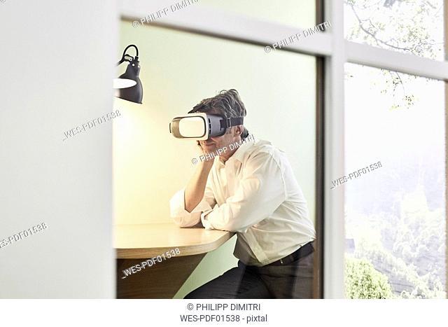 Businessman wearing VR glasses in modern office