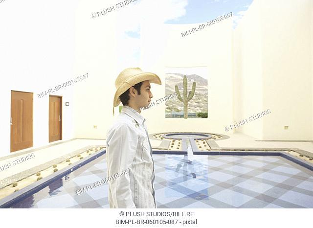 Man in cowboy hat walking past a hotel pool, Los Cabos, Mexico