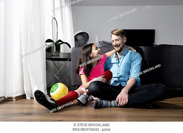 Girl in soccer outfit sitting next to father on floor in living room