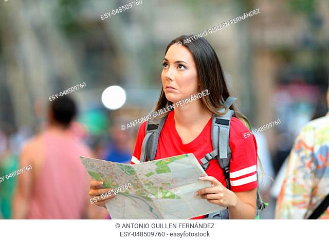Confused teen tourist holding a paper guide looking above on the street