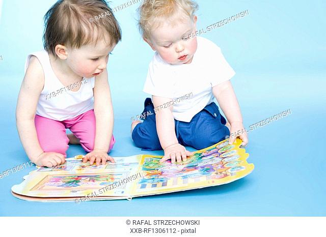 toddler boy and toddler girl looking at book